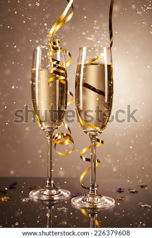 Glasses of champagne with ribbons and bubbles around. Concept of celebration #226379608