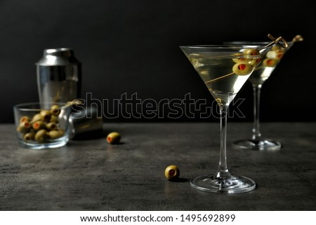 Glasses of Classic Dry Martini with olives on grey table against black background Foto stock ©