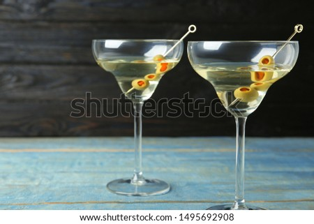 Glasses of Classic Dry Martini with olives on light blue wooden table against dark background #1495692908
