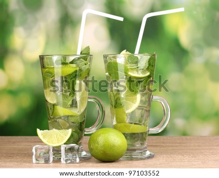 Glasses of cocktail with lime and mint on wooden table on green background