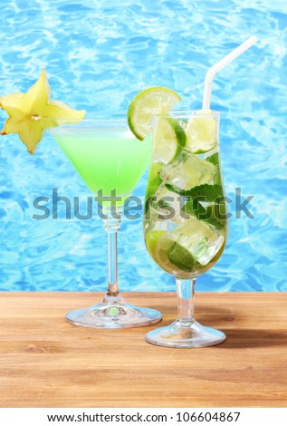 Glasses of cocktails on wooden table on blue sea background