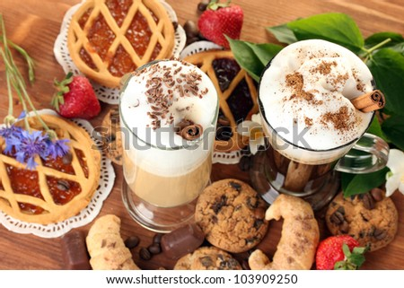 glasses of coffee cocktail on wooden table with sweet and flowers