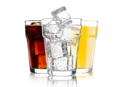 Glasses of cola and orange soda drink and lemonade sparkling water on white background with ice cubes