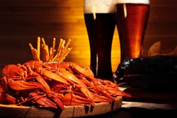 Glasses of dark and light beer with crawfish and smoked fish