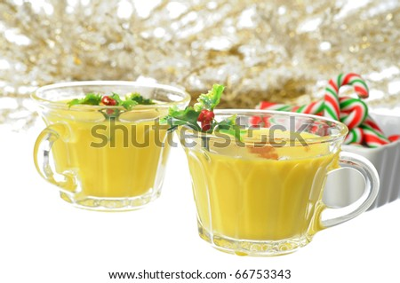 Glasses of delicious eggnog garnished with holly. - stock photo