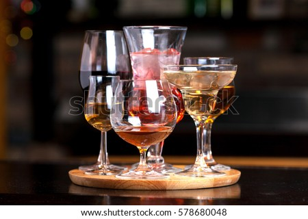 glasses of different shapes with different alcohol on a wooden round board on the bar #578680048