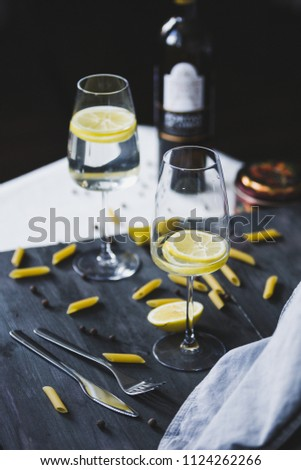 glasses of home lemonade and bottle of wine for italian dinner with pasta, pepper and lemon on the grey wooden background and two kind of textile #1124262266