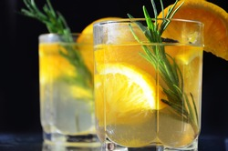 glasses of honey bourbon cocktail with rosemary whiskey sour drink with orange peel, or winter warmer drink punch or mulled wine christmas party cocktail or detox, healthy drink for diet, vitamin c