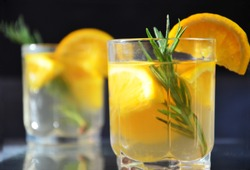 glasses of honey bourbon cocktail with rosemary whiskey sour drink with orange peel, or winter warmer drink punch or mulled wine christmas party cocktail or detox, healthy drink for diet, vitamin c.