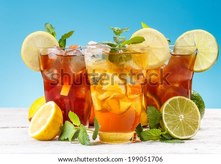 Glasses of iced tea with lemon, lime, orange and ice cubes