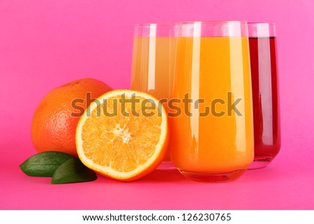 Glasses of juise with leafs and fruits on pink background