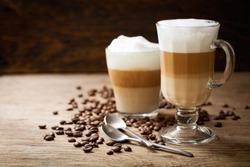 glasses of latte macchiato coffee on a wooden background