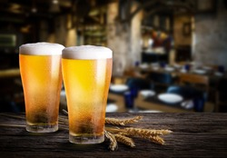 Glasses of light beer with barley on a pub background