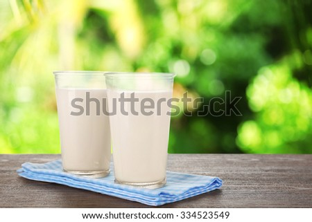 Glasses of milk on wooden table against blurred nature background #334523549