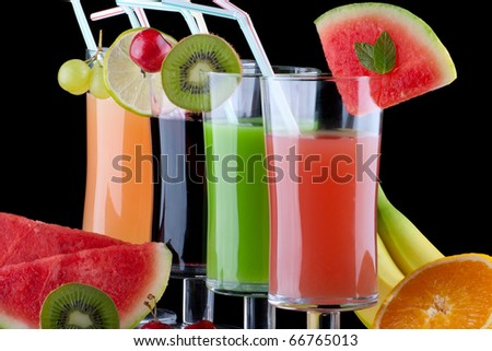 Glasses of organic juice made from fresh fruits and surrounded by fresh ones. Series about organic and healthy drinks.