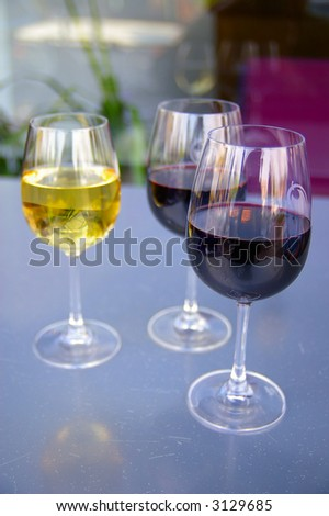 Glasses of red and white wine at an outdoor cafe