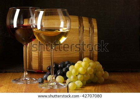 Glasses of red and white wine, grape and souvenir barrel on wooden surface.