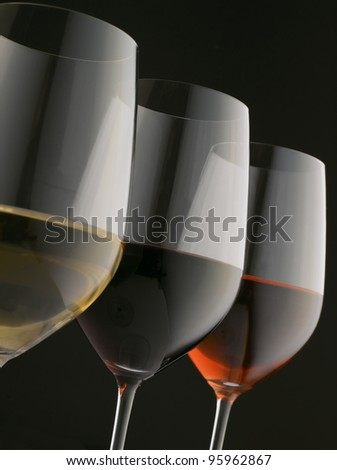 Glasses of red, white and rose wine on black background (Shallow focus. Focus on red wine)