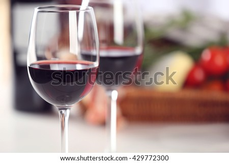 Glasses of red wine with food on table closeup #429772300