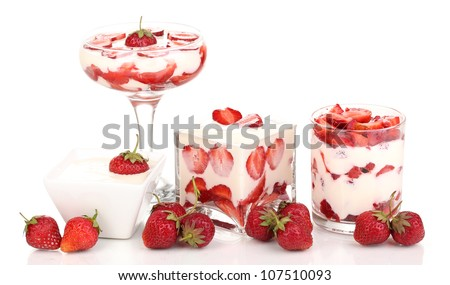 Glasses of ripe strawberries with cream isolated on white