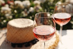 Glasses of rose wine on white table in blooming garden, closeup. Space for text