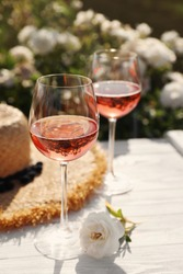 Glasses of rose wine, straw hat and beautiful flower on white wooden table outdoors