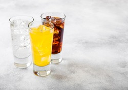 Glasses of soda drink with ice cubes and bubbles on stone kitchen background.
