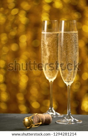 Glasses of sparkling wine on the background of golden bokeh.Celebration theme with champagne still life #1294281214