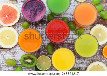Glasses of tasty fresh juice, on wooden desk. Unusual top view