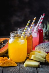Glasses of tasty fresh tropical juices with fresh tropical fruits, Papaya Pine Apple Mango Dragon on dark background.