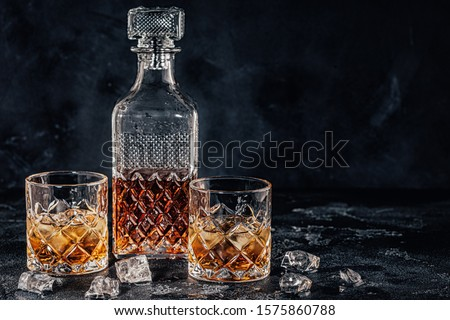 Glasses of the whiskey with a square decanter on a black stone background. ストックフォト ©