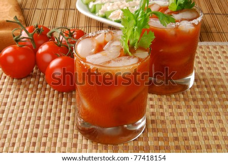 Glasses of tomato juice with tomatoes on the vine - or a Bloody Mary cocktail