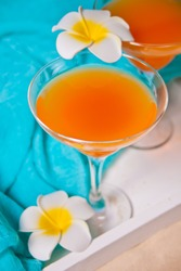 Glasses of tropical exotic multifruit juice cocktail drink on the white tray with plumeria frangipani flower. Tripical beach picnic concept.