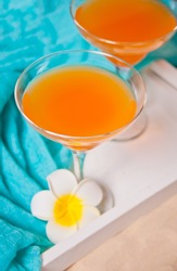 Glasses of tropical exotic multifruit juice cocktail drink on the white tray with plumeria frangipani flower. Tripical beach picnic concept