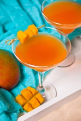Glasses of tropical exotic multifruit mango juice cocktail drink on the white tray. Tripical beach picnic concept.
