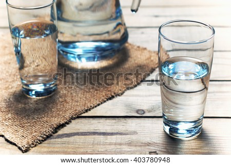 Glasses of water on a wooden table. Selective focus. Shallow DOF