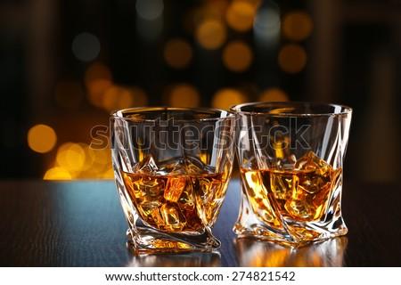 Glasses of whiskey on bar background