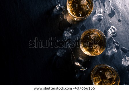 Glasses of whiskey with ice cubes on dark table Foto stock ©