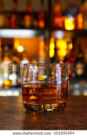 glasses of whisky on a dark wooden table in the background of light bar