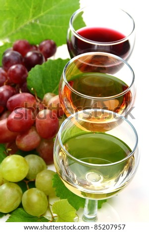 Glasses of white, pink, red wine and grape on white background.
