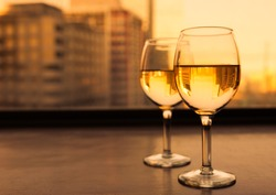 Glasses of white wine with city view.