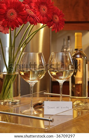 Glasses of white wine with gerbera daisies on counter in the kitchen