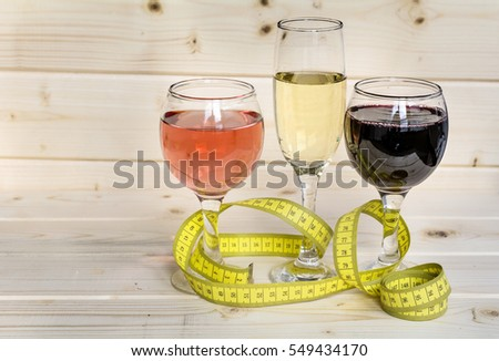 glasses of wine and champagne with  measuring tape.Calories in alcohol are extra-fattening