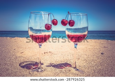 Glasses of wine and cherries on the beach, romance near the sea - retro and vintage style