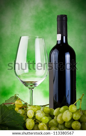 Glasses of wine and grapes on green background