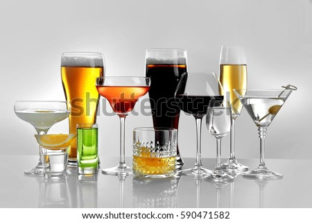 Glasses of wine and spirits on light background