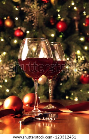 Glasses of wine in front of Christmas tree for the holidays