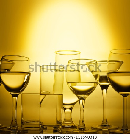 Glasses  of wine in gold color on silhouette of black on a bright Sunny background