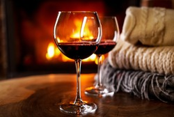 Glasses of wine, knitwear and blurred fireplace on background