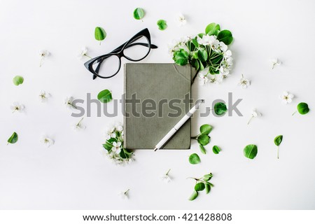 Glasses, old book, pen and branches with leaves and flowers on white background. Flat lay composition